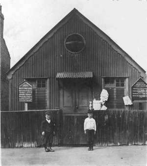 Church Hall in Sutcliffe Road just off                             the Slade. Alf Hall (the dwarf man) worked                             at Mackintoshes as maintenance engineer and                             because he was smaller than most was able to                             get into very tight places. Mackintoshes was                             at the bottom of Kings Highway. The boy is                             Fred Smith. The photo is c. 1918. Photo:                             John Miles