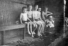 Colin, Arthur (Collins), John, Mark,                           Brian (Collins) with Ann Weightman in                           pushchair c.1949 in the paddling pool changing                           shed. Photo: Colin Weightman                           See story Clean Lake, Dirty Lake, Our Lake                           Districts and The Boy & The Country Tramp